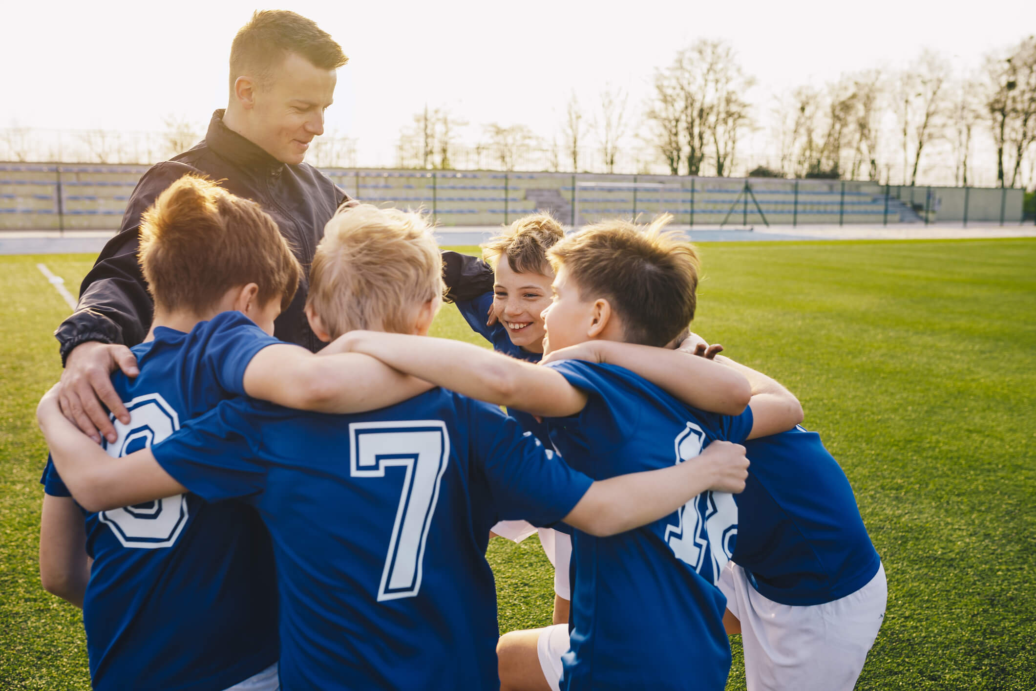Group Of Children In Soccer Team Celebrating With Coach